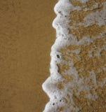Schaumige Ozeanwelle auf einem sandigen Strand Stockfotos
