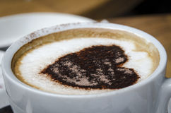 Schaumige Spitze eines Tasse Kaffees mit Herzmuster Stockfotografie
