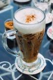 Schaumiger, überlagerter Cappuccino in einem Klarglas Lizenzfreie Stockbilder