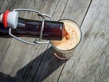 Schaumiges dunkles Bier, das in hohe Gläser von einer braunen Glasflasche im Sommergarten auf rustikalem Holztisch gießt Lizenzfreies Stockfoto