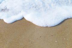 Schaummeer auf dem Sand Hintergrund stockfoto