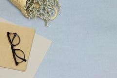 Schauspiele auf dem gelben Anmerkungsbuch, rosa Papiere, Korb mit Blumen lizenzfreie stockfotos