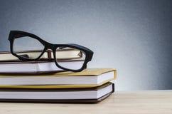 Schauspiele auf Stapel Büchern über schönem Steigungshintergrund mit Echo lizenzfreie stockbilder