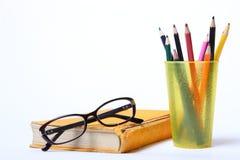 Schauspiele, die auf altem Buch liegen Bleistifte in einem Glas Stockfotos