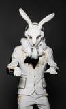 Schauspieler, der in der weißen Kaninchenklage mit Kopfhörern aufwirft Stockbild