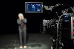 Schauspieler vor der Kamera Lcd-Anzeige auf dem Kamerarecorder Schmierfilmbildung im Innenraum stockfoto