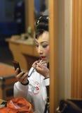 Schauspielerin ist Anstrich ihre Gesichts-Bühne hinter dem Vorhang Lizenzfreie Stockfotos