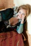 Schauspielerin mit einem Apfel im mittelalterlichen Kleid liegt auf Hintergrund des Innenraums Stockfoto