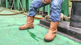 Schaute Schuhe und Jeans einer Arbeitskraft, die saß Stockfotografie