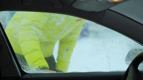 Schavend sneeuw en ijs van autowindscherm Opgeheven ruitewissers de nacht voordien om hen bevroren te verhinderen wordend stock video