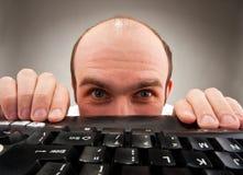Schüchterner Sonderling, der unter Computertastatur sich versteckt Stockfoto