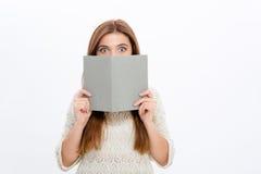 Schüchternes verlegenes junges weibliches Verstecken hinter grauem Buch Lizenzfreies Stockfoto