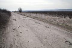 Schädigende Asphaltpflasterungsstraße mit den Schlaglöchern verursacht durch Frost und Tauwetterzyklus während des Winters Stockfotografie