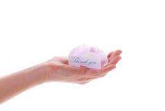 Scheda con ringraziamento e un fiore in sua mano Immagine Stock