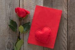 Scheda del `s del biglietto di S Rosa rossa, cuore e taccuino rosso sul bordo di legno Vista superiore Fotografia Stock Libera da Diritti