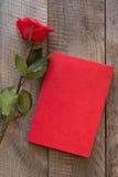 Scheda del `s del biglietto di S Rosa rossa e taccuino di rosso sul bordo di legno Fotografie Stock
