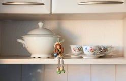 Scheda dell'armadio da cucina con una bambola e le tazze Immagini Stock Libere da Diritti