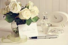 Scheda di nota con le rose e la penna bianche fotografia stock