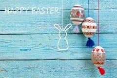 Scheda di pasqua felice Uova di Pasqua e coniglio brillanti variopinte sul fondo di legno blu della tavola Copi lo spazio per tes Fotografie Stock