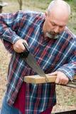 Scheda di taglio dell'uomo con la sega della mano Immagine Stock Libera da Diritti