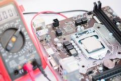 Scheda madre del computer e del multimetro con il CPU Fotografie Stock