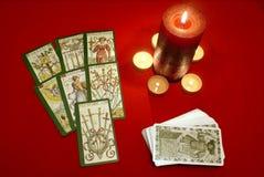 Schede di Tarot con le candele sulla tessile rossa Fotografia Stock