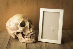 Schedel en houten kaderstilleven op houten achtergrond Stock Afbeeldingen