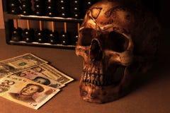 Schedel op oud hout met bankbiljetyuans en dollar in stilleven stock fotografie
