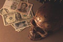 Schedel op oud hout met bankbiljetyuans en dollar in stilleven stock foto's