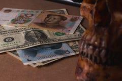 Schedel op oud hout met bankbiljetyuans en dollar in stilleven royalty-vrije stock afbeelding