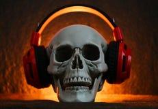 Schedelmuziek met hoofdtelefoon/Menselijke schedel die aan muziekoortelefoon luisteren die bij Halloween-partij wordt verfraaid stock foto's