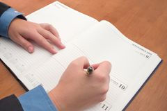 Schedule. Businessperson writing in diary Stock Images
