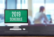 2019 schedule on desktop computer on black board wooden table top with blur people working at office desk bokeh background.  stock photos