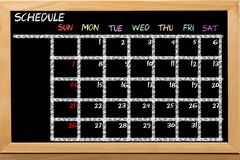 Schedule with grid time table on black chalkboard background stock images