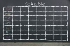 Schedule with grid time table on black chalkboard background. Business and education concept stock image