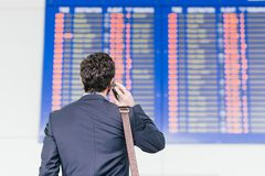 Schedule. Man looking at the airline schedule and talking on the phone, rear view royalty free stock images