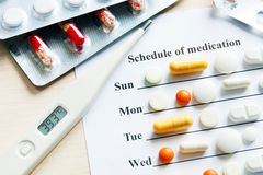 Schedule of medication for a week with various pills and thermometer Royalty Free Stock Photos