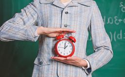 Schedule and regime. Alarm clock in female hands close up. Teachers attributes. Alarm clock in hands of teacher or stock photo