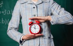 Schedule and regime. Alarm clock in female hands close up. Teachers attributes. Alarm clock in hands of teacher or royalty free stock photos
