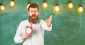 Schedule and regime concept. Bearded hipster holds clock, chalkboard on background, copy space. Man with beard on. Shouting face on arguing expression. Teacher royalty free stock photo