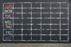 Schedule of the week with grid on black chalkboard background. Business or education concept royalty free stock photography