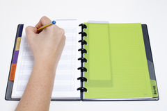 Scheduling the day. Writting appointments on a green agenda Stock Image
