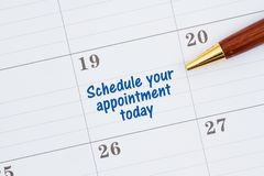Scheduling your appointment today on a monthly calendar. With a pen stock photo