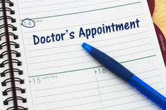 Scheduling your doctor`s appointment. A day planner with blue pen with text Doctor`s Appointment stock photos