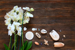 Scheerapparaatdepilator met orhides en shells op donkere houten Royalty-vrije Stock Afbeelding