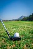 Scheggia della palla da golf sul verde con il club di golf del driver Immagine Stock