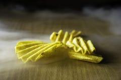 Scheggia le patatine fritte, il fumo, la tavola di legno, giallo, ribbed fotografia stock libera da diritti