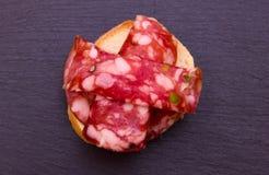 Scheibe brot mit Scheiben der Salami mit Pistazien auf Spitzenschiefer Stockbilder