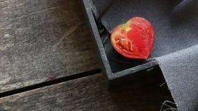 Scheibe der frischen Tomate in der Herzform auf Weinlesetabelle stock video