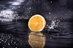 Scheibe der frischen Zitrone über dem dunklen Hintergrund mit Wasser Lizenzfreies Stockfoto